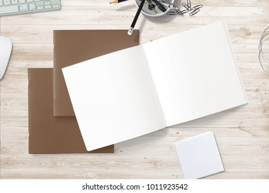 Square Magazines with carton soft cover and blank pages on wooden desk. 3d illustration for your presentation.