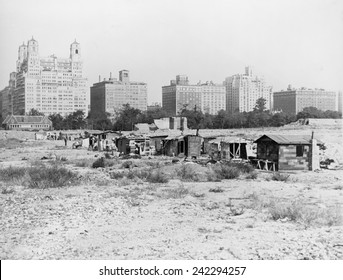Squatter's shacks in Central Park with the landmark Dakota Apartment building in the background. The Hooverville grew up at a construction site where work was suspended.