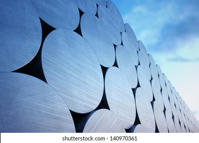Stack of aluminium billets on a cloudy sky background. Suitable for any industrial related purposes.