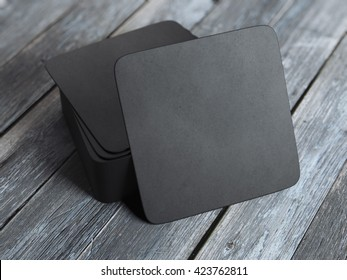 Stack of black square beer coasters on wooden table. 3d rendering