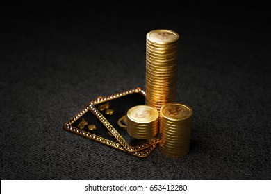 Stack of gold coins on texas hold'em poker cards with two ace of spades. 3D illustration on black background.