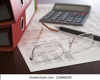 Stack of ring binders, documents, calculator, pen and glasses at workplace