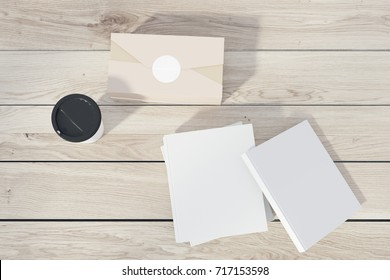 Stack of white books lying on a wooden table, a paper cup of coffee and a closed box. Top view. 3d rendering mock up