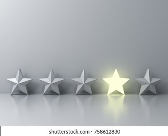 Stand out from the crowd and different creative idea concepts , One glowing star standing among other dim stars on grey background with reflections and shadows . 3D rendering.