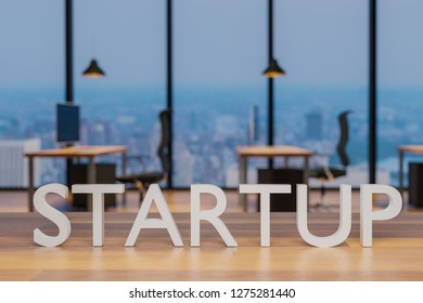 startup logo on clean wooden desk in modern office with skyline view 3d rendering