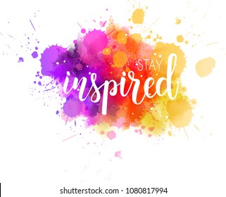 Stay inspired hand lettering phrase on watercolor imitation color splash.  Modern calligraphy inspirational quote.