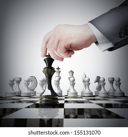 Strategy concept. hand holding black chess figure on chess board