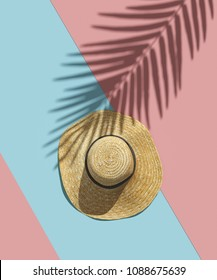 Straw hat and shadow of tropical palm leaves on bright pink blue stripes background . Minimal summer concept. Creative flat lay. 3D illustration