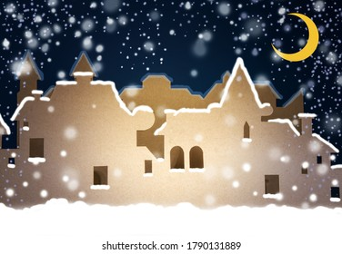 A street of houses in two rows, cut out of cardboard, imitating a small European city on a dark blue background fnd snow