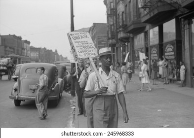 Striking workers picketing a reality company. Sign reads 'Mid City Reality Unfair-Underpays the Workers-Overcharges the Tenants-Support the Strike'. New York City ca. 1936-42.