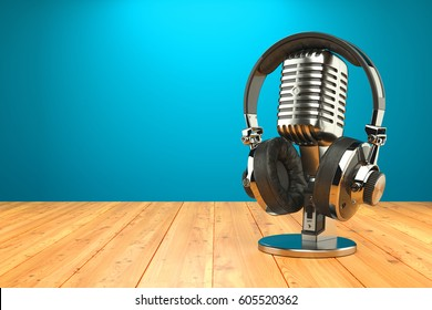 Studio microphone and professional headphones on wood table