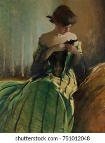 STUDY IN BLACK AND GREEN, by John White Alexander, 1909, American painting, oil on canvas. A young women pins an ornament to the low neckline of her two-toned evening gown with a striped skirt. She we