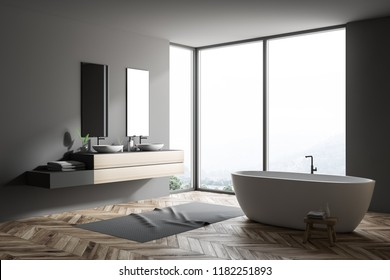 Stylish gray bathroom interior with wooden floor, gray rug, window with forest view, wooden wall, big bathtub, and double sink with vertical mirrors. 3d rendering copy space