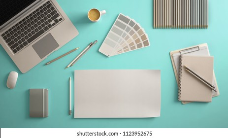 Stylish minimal office table desk. Workspace with laptop, notebook, pencils, coffee cup and sample color palette on pastel turquoise background. Flat lay, top view, blank paper mockup template, 3d ill