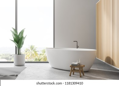 Stylish white bathroom interior with concrete floor, gray rug, window with tropical view, wooden wall, big bathtub, and a potted plant. 3d rendering copy space