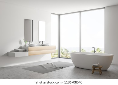 Stylish white bathroom interior with concrete floor, gray rug, window with tropical view, wooden wall, big bathtub, and double sink with vertical mirrors. 3d rendering copy space