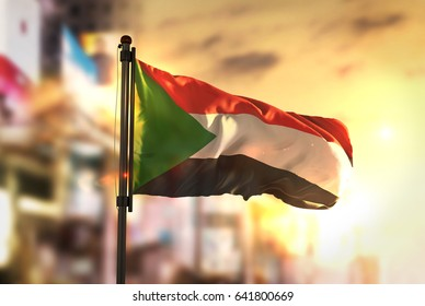 Sudan Flag Against City Blurred Background At Sunrise Backlight 3D Rendering