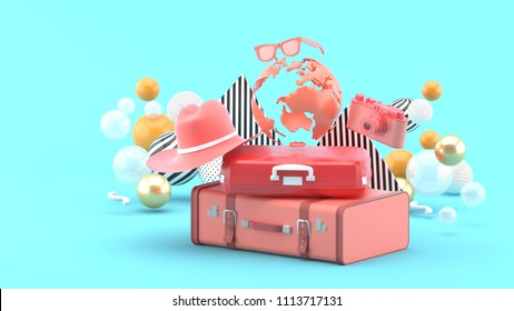 A suitcase under the globe surrounded by a camera and hat on an blue background.-3d rendering.