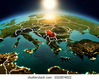 Sunrise above Serbia highlighted in red on model of planet Earth in space with visible country borders. 3D illustration. Elements of this image furnished by NASA.