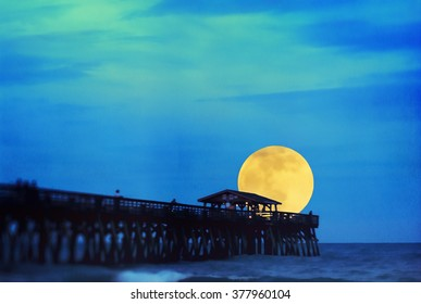 Supermoon at Myrtle Beach State Park pier in Myrtle Beach South Carolina USA. This is computer generated art from a photograph.