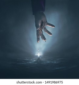 A surreal digital illustration of the hand of Jesus above a man who is glowing bright white.
