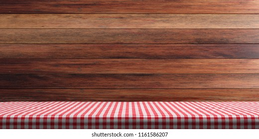 Table covered with red checkered tablecloth on wooden wall background, copy space. 3d illustration