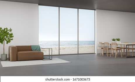 Table on concrete floor of large dining room near living area and sofa in modern beach house or luxury hotel. Minimal home interior 3d rendering with sea view.