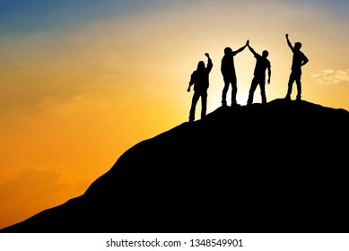 Team of people work on peak mountain with sunset background ,teamwork success business  winner concept