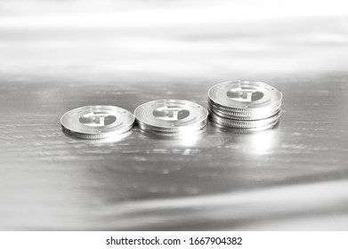Tether (USDT) digital crypto currency. Stack of silver coins against the background of numbers. Cyber money. 3D Render.