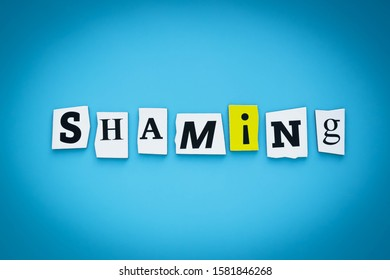 Text - shaming. Single word. Cut paper letters on blue background. Writing on banner, card. Inscription, message on poster.