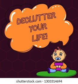 Text sign showing Declutter Your Life. Conceptual photo remove unnecessary items from untidy overcrowded place Baby Sitting on Rug with Pacifier Book and Blank Color Cloud Speech Bubble.