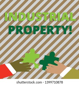 Text sign showing Industrial Property. Conceptual photo the intangible ownership of a trademark or patent Two Hands Holding Colorful Jigsaw Puzzle Pieces about to Interlock the Tiles.