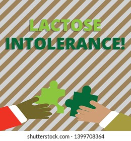 Text sign showing Lactose Intolerance. Conceptual photo digestive problem where body is unable to digest lactose Two Hands Holding Colorful Jigsaw Puzzle Pieces about to Interlock the Tiles.