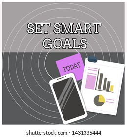 Text sign showing Set Smart Goals. Conceptual photo giving criteria to guide in the setting of objectives Layout Smartphone Off Sticky Notes Clipboard with Pie Chart and Bar Graph.
