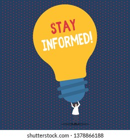 Text sign showing Stay Informed. Conceptual photo Knowing what you may encounter what do before after any hazard Person Standing and Raising Up Arms Holding Big Yellow Lightbulb for Ideas.