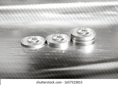 Tezos (XTZ) digital crypto currency. Stack of silver coins against the background of numbers. Cyber money. 3D Render.