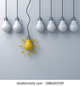 Think different concept , One hanging yellow idea bulb standing out from the dim unlit light bulbs on white wall background , leadership and individuality creative idea concepts . 3D rendering.