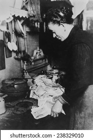 This Berlin woman, realizing that fuel costs money, is starting the morning fire with marks...', Germany, ca 1920s.