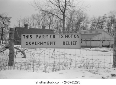 'This Farmer is not on Welfare ' reads a sign a wire fence. Iowa or Illinois Dec. 1940.