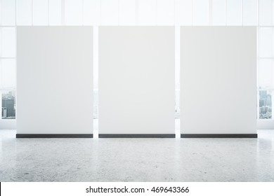 Three blank posters in interior with concrete floor and window with city view. Mock up, 3D Rendering