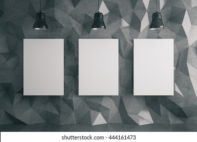 Three blank posters in room with dark polygon patterned wall and ceiling lamps. Mock up, 3D Rendering