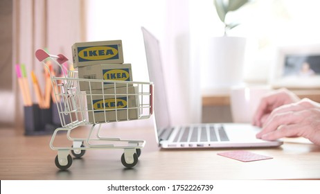 Three cartons with IKEA logo in shopping trolley near customer with laptop. Editorial online shopping from home 3D rendering