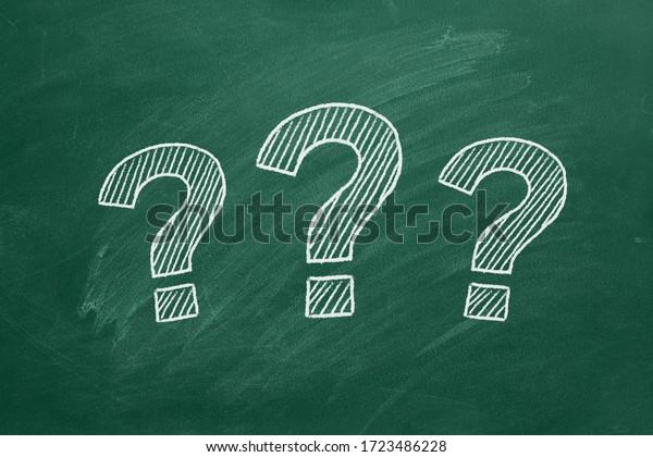 Three question marks drawn in chalk on a greenboard