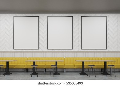 Three vertical framed posters on a cafe wall with yellow sofas and small wooden tables. 3d rendering. Mock up.