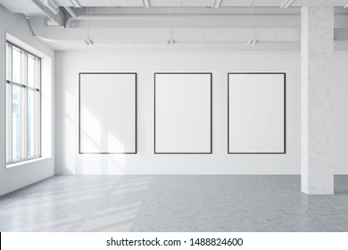 Three vertical mock up poster frames hanging in modern industrial style gallery with white walls, concrete floor, windows with cityscape and pipes. Concept of advertising and art. 3d rendering