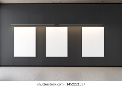 Three vertical mock up posters hanging in gallery interior with gray walls, concrete floor and wooden ceiling. Concept of advertising. 3d rendering