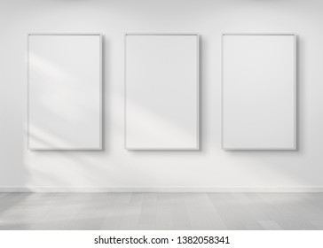 Three white frames hanging on a white wall mockup 3d rendering