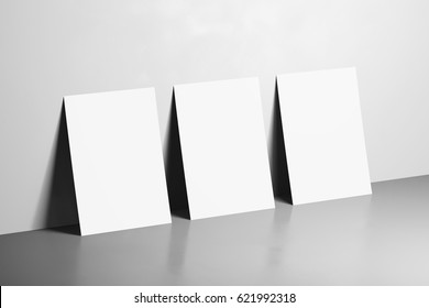 Three White Posters Mockups on grey background with a reflection. 3d rendering