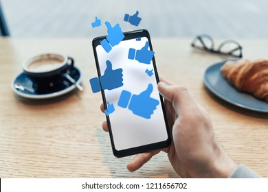 Thumbs up blue symbols on blank mobile phone screen. Close up of man hand holding mobile phone in cafe. 3d rendering. Social media concept.
