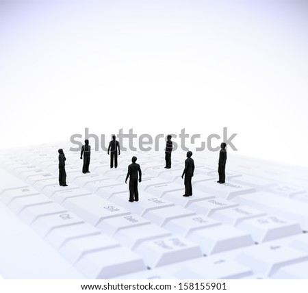 Tiny people standing on a computer keyboard